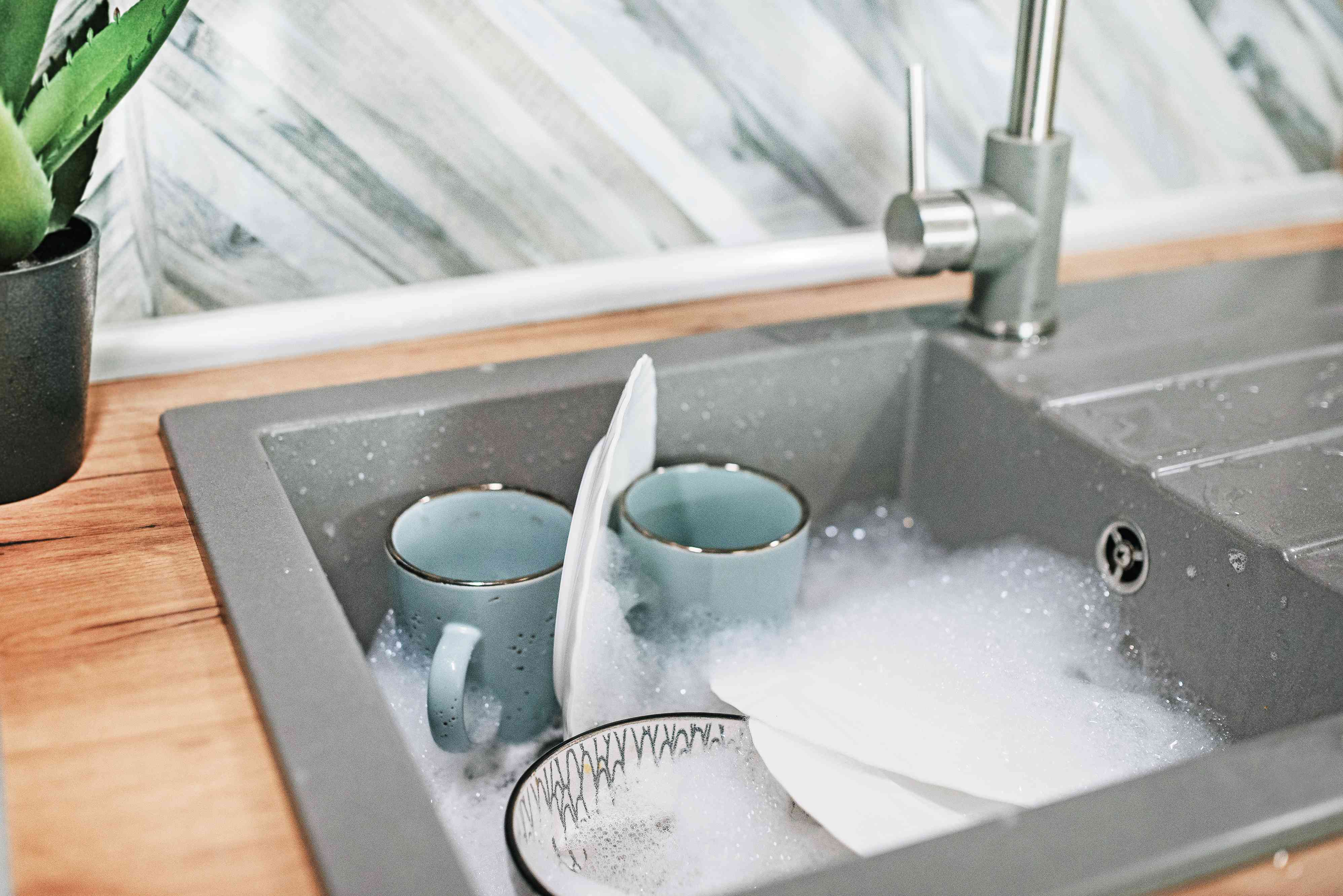 Dishes soaked in kitchen sink with soapy water