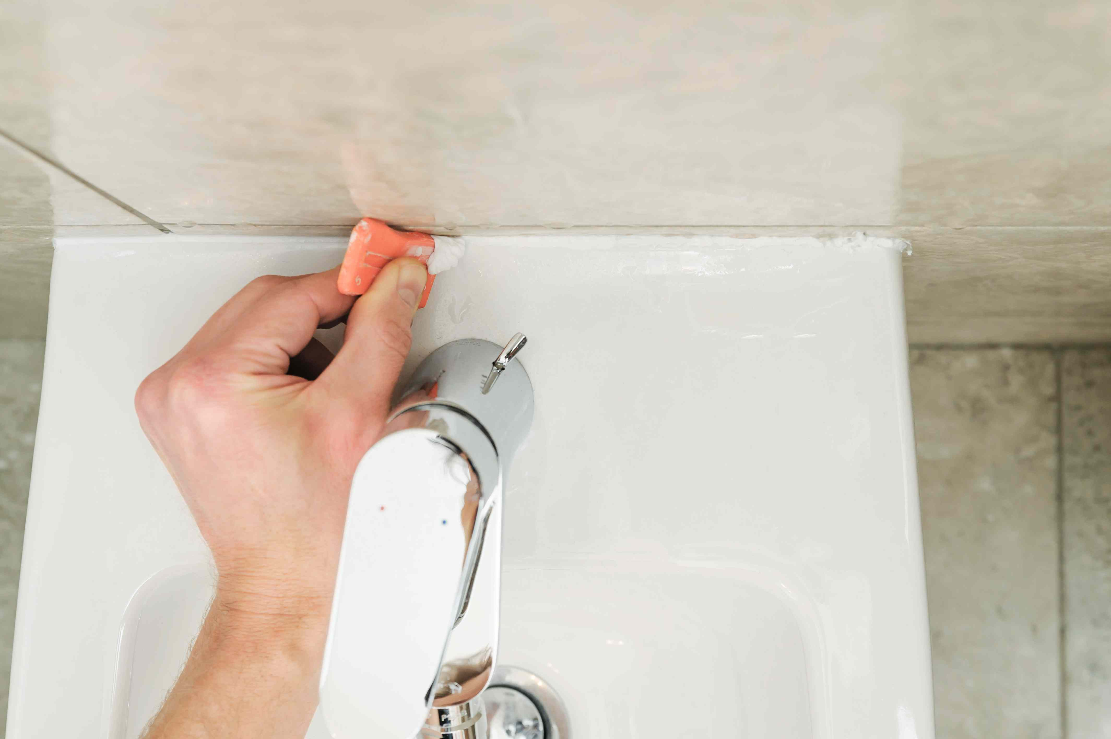 Worker smoothing silicone sealant.
