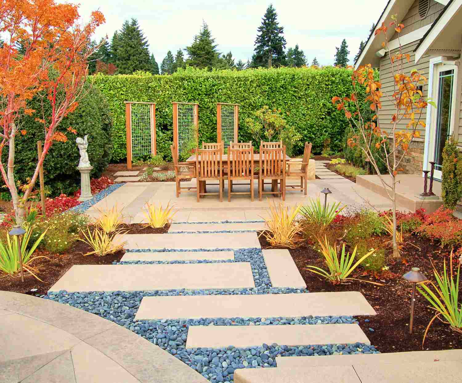 Vertical garden for patio with wooden table and chairs and stone walkway.