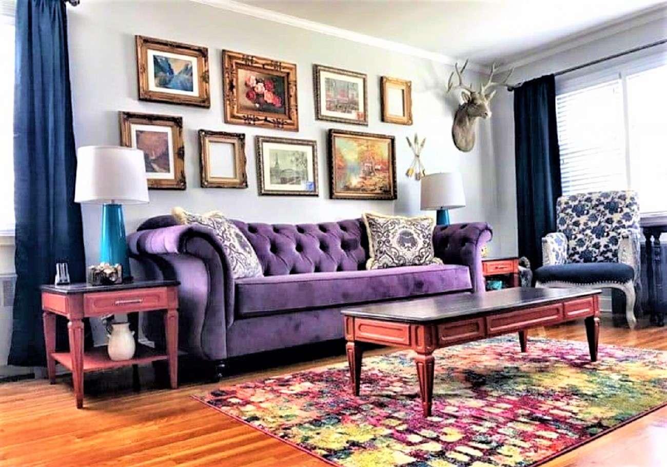 Ecléctico,sala de estar colorida con paredes azuladas, sofá morado, mesa auxiliar y mesa de centro con alfombra colorida