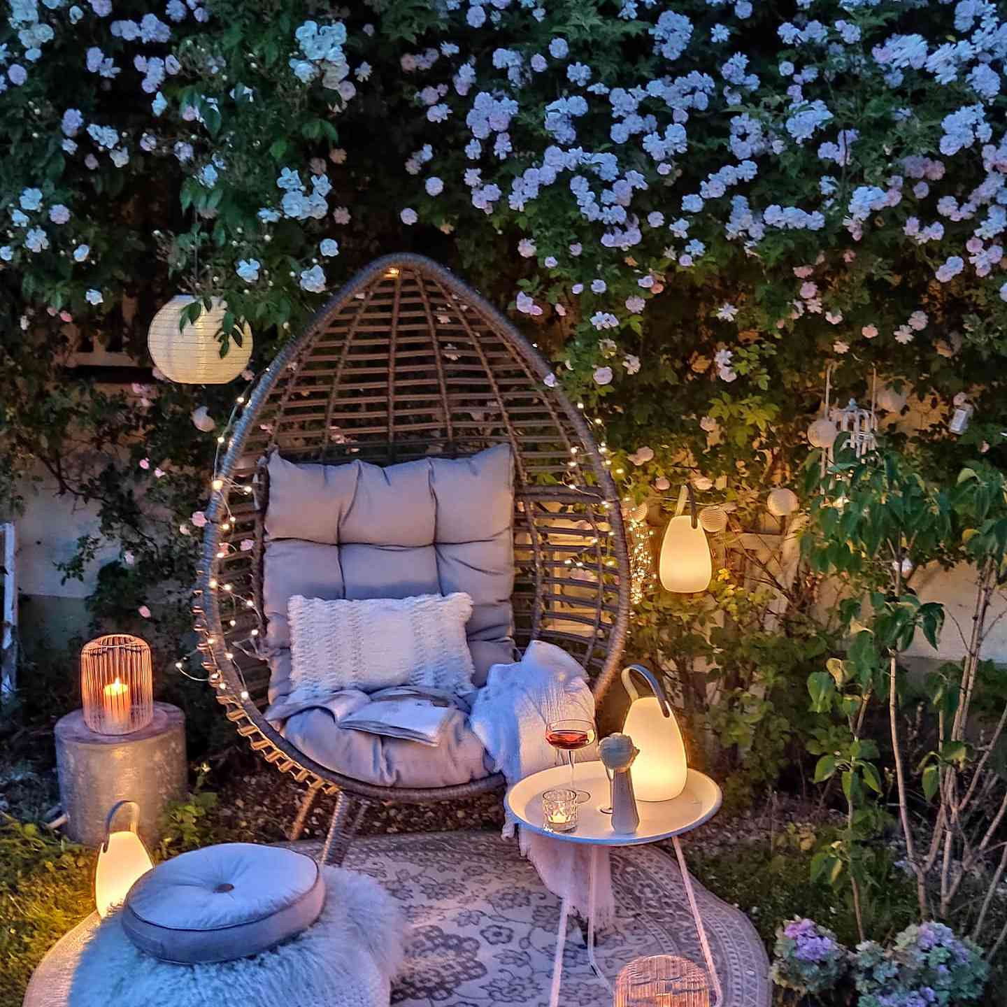 a cocoon chair is surrounded by soft lighting, a rug, and a blooming tree for the prettiest and coziest backyard retreat