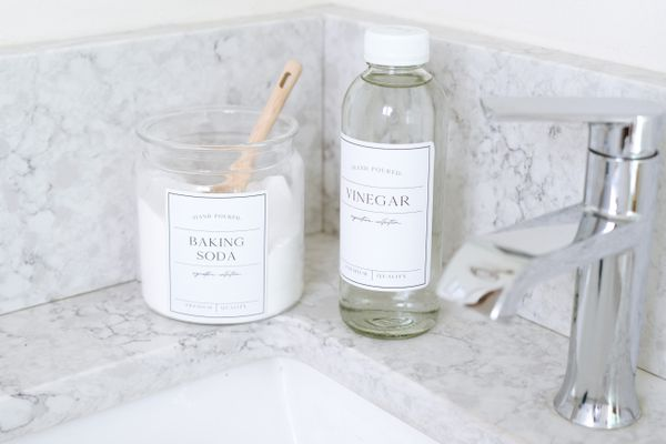 Baking soda and white vinegar in glass containers on corner of bathroom sink