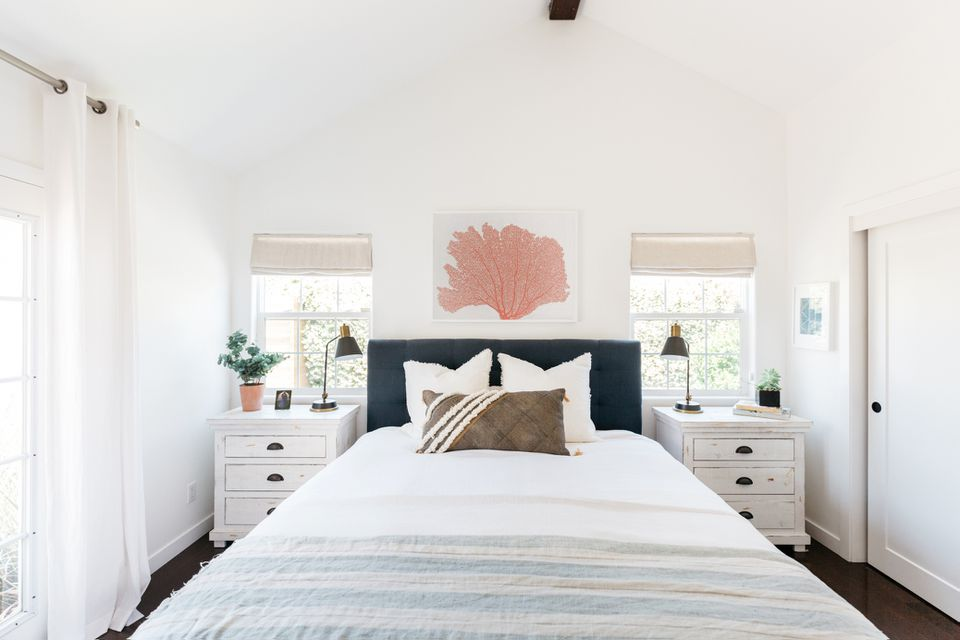 Beach-inspired bedroom with light colored linens on bed and red coral print above