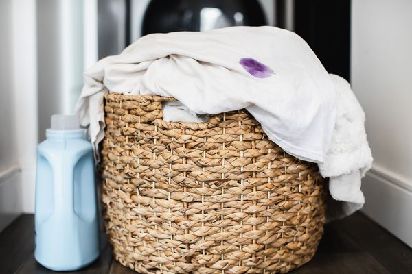 Woven basket with fabrics hanging over with purple stain next to laundry detergent bottle