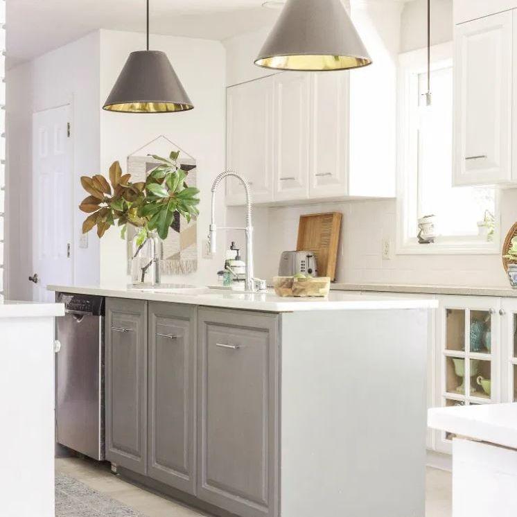 Cocina actualizada con isla gris y gabinetes blancos.