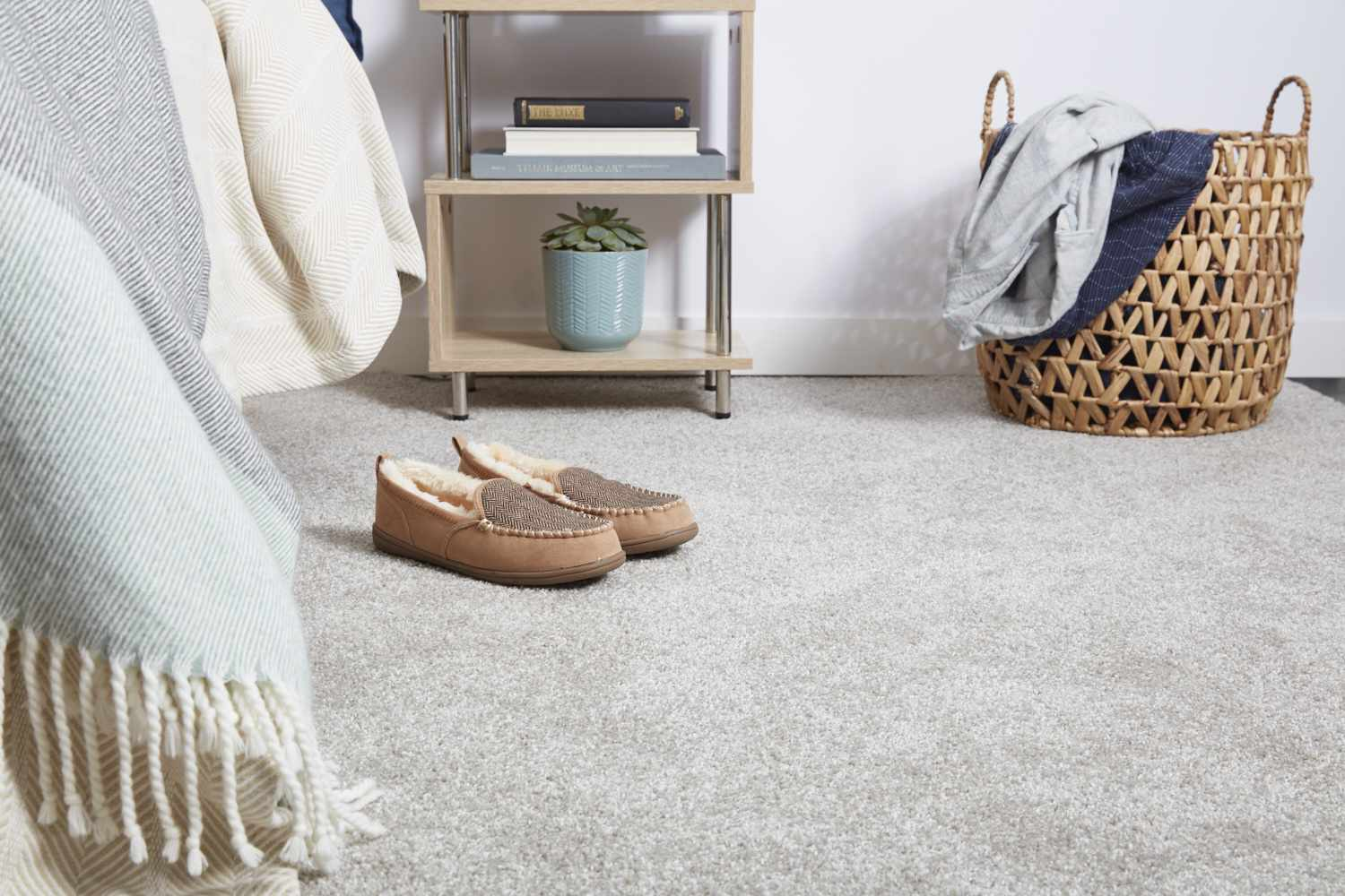 Carpet flooring with with wool shoes next to bed and woven hamper, in front of nightstand