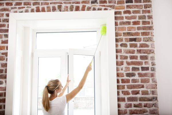 Woman dusting tall window frame with extendable duster on brick wall