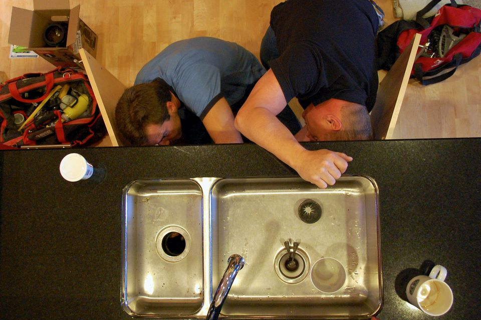 plumbers fixing a kitchen garbage disposal