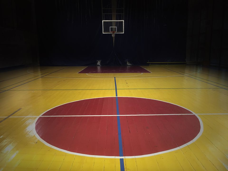 A dimly light empty basketball Court