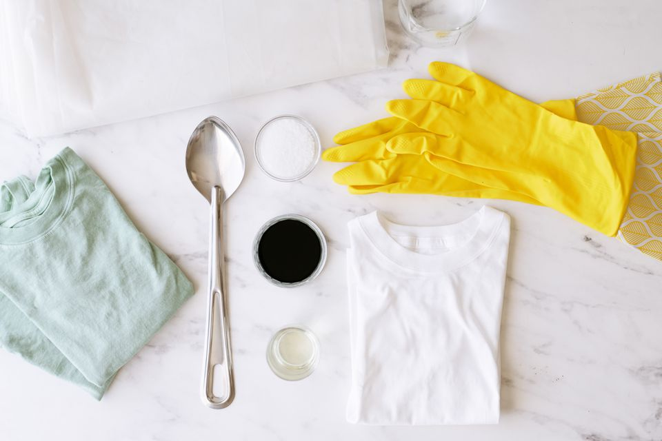 Liquid fabric dye with shirts and yellow gloves