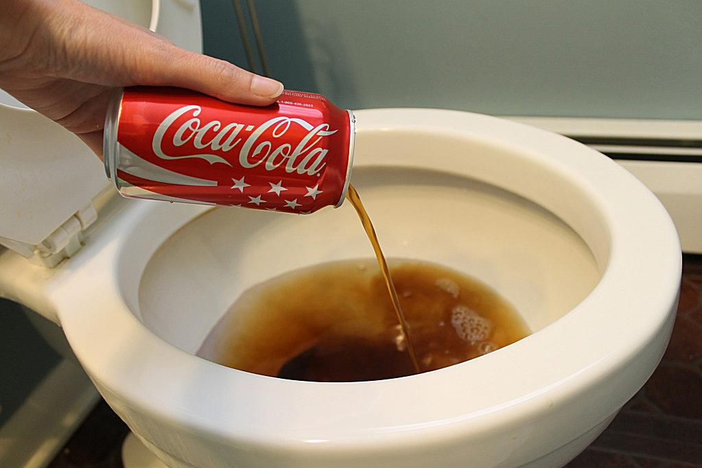 Dumping a can of Coke into a toilet