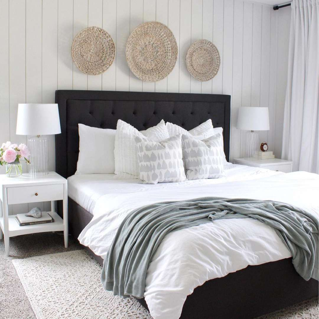 white bedroom with baskets on walls