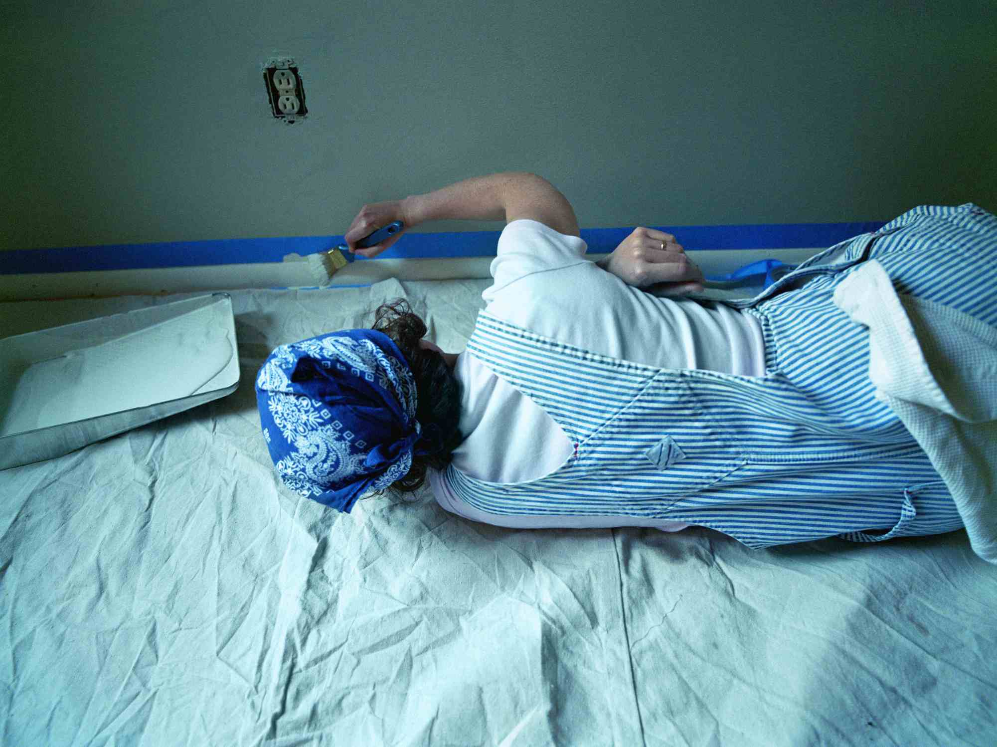 Woman lying on floor, painting wall trim, rear view