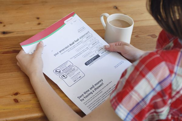Young person looking at utility bill with a cup of coffee.