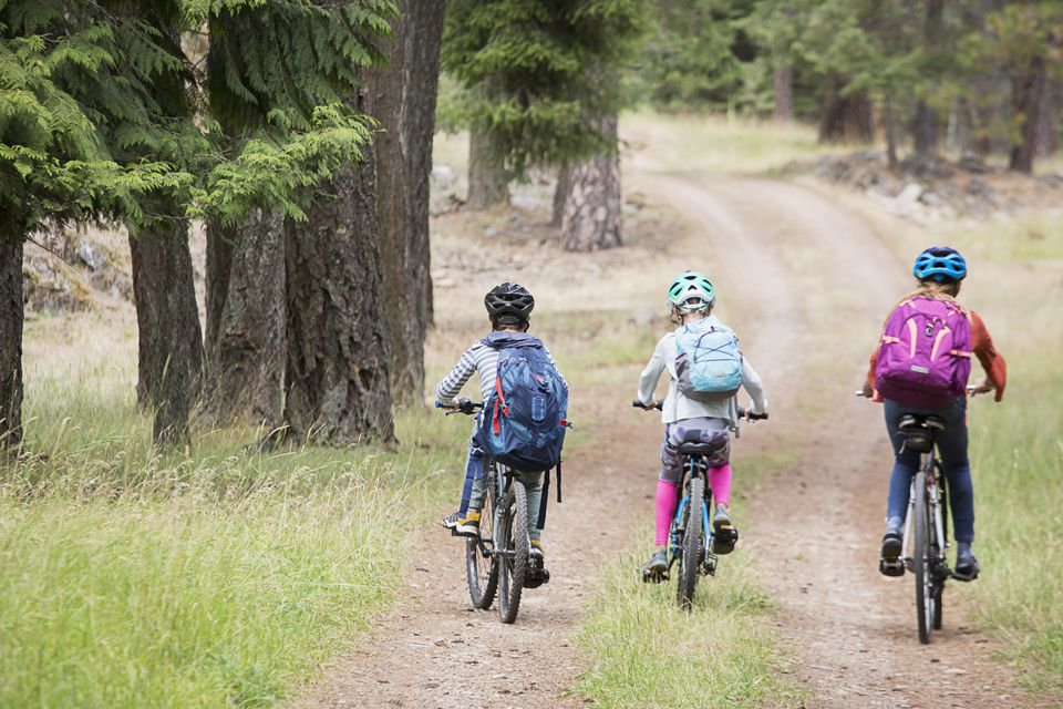 Three kids on bikes wearing backpacks