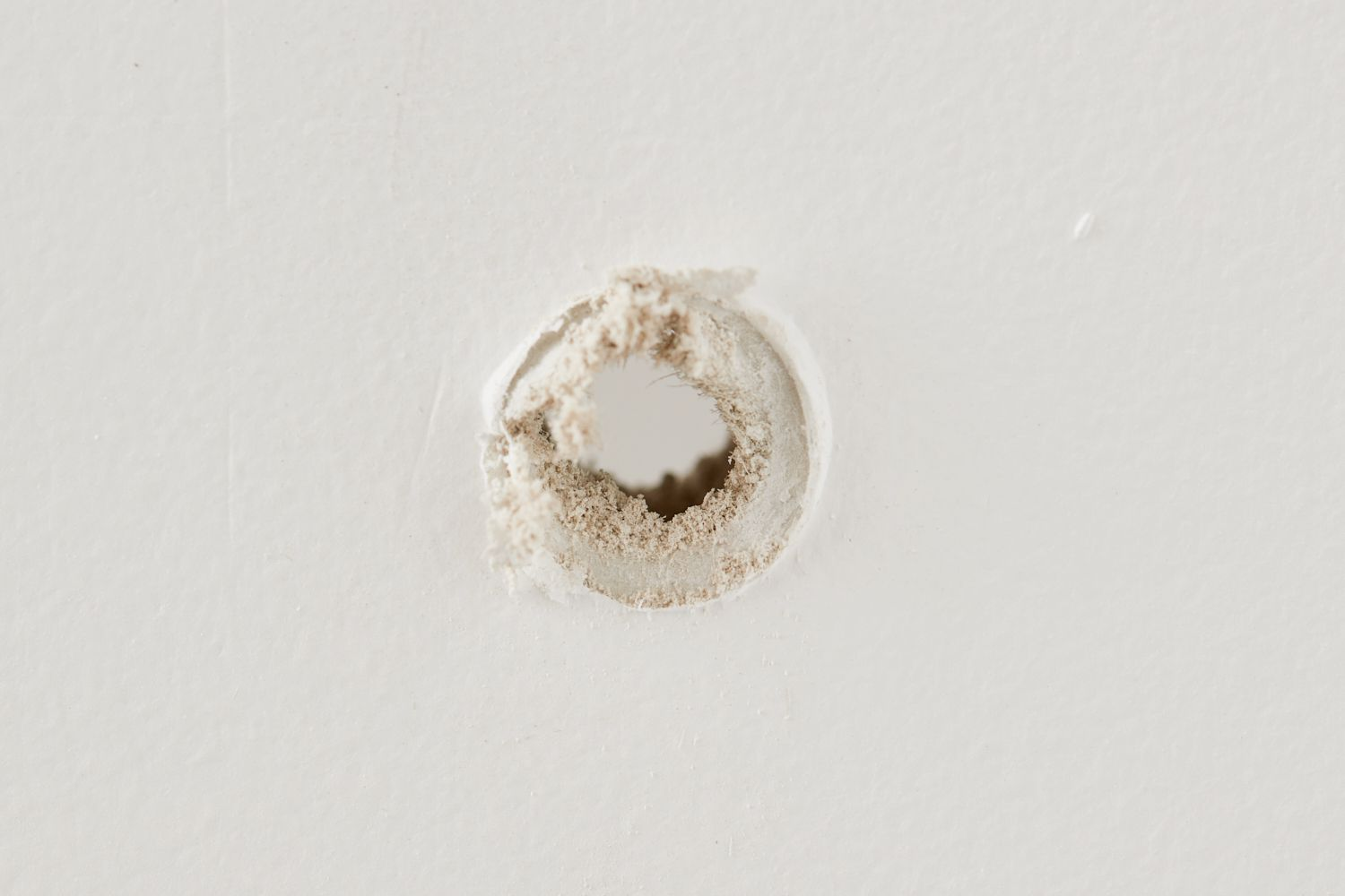 inspecting the drywall hole