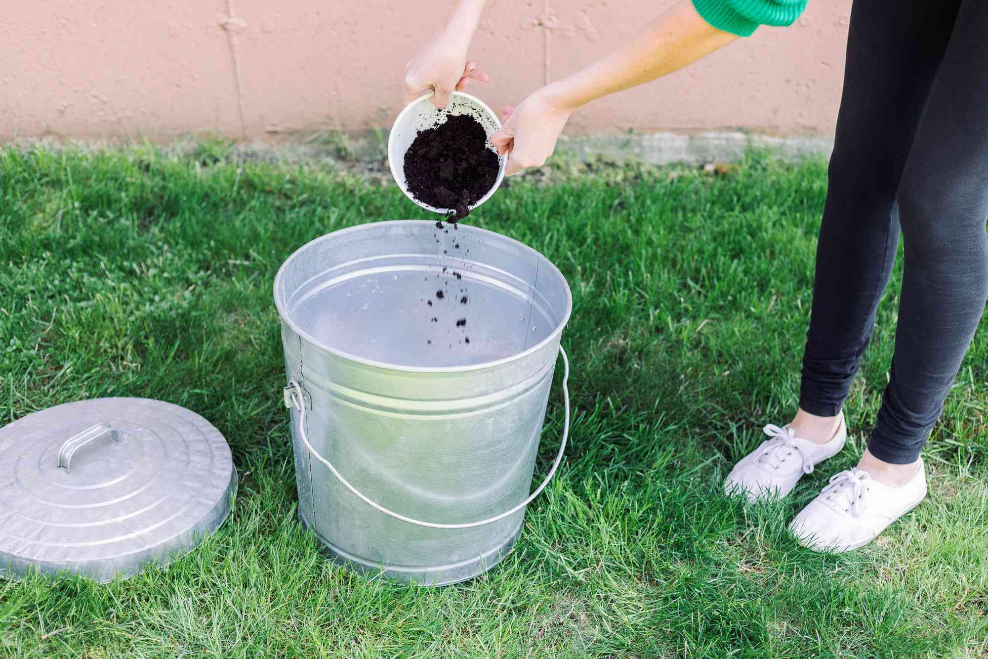 adding coffee grounds to a compost bin
