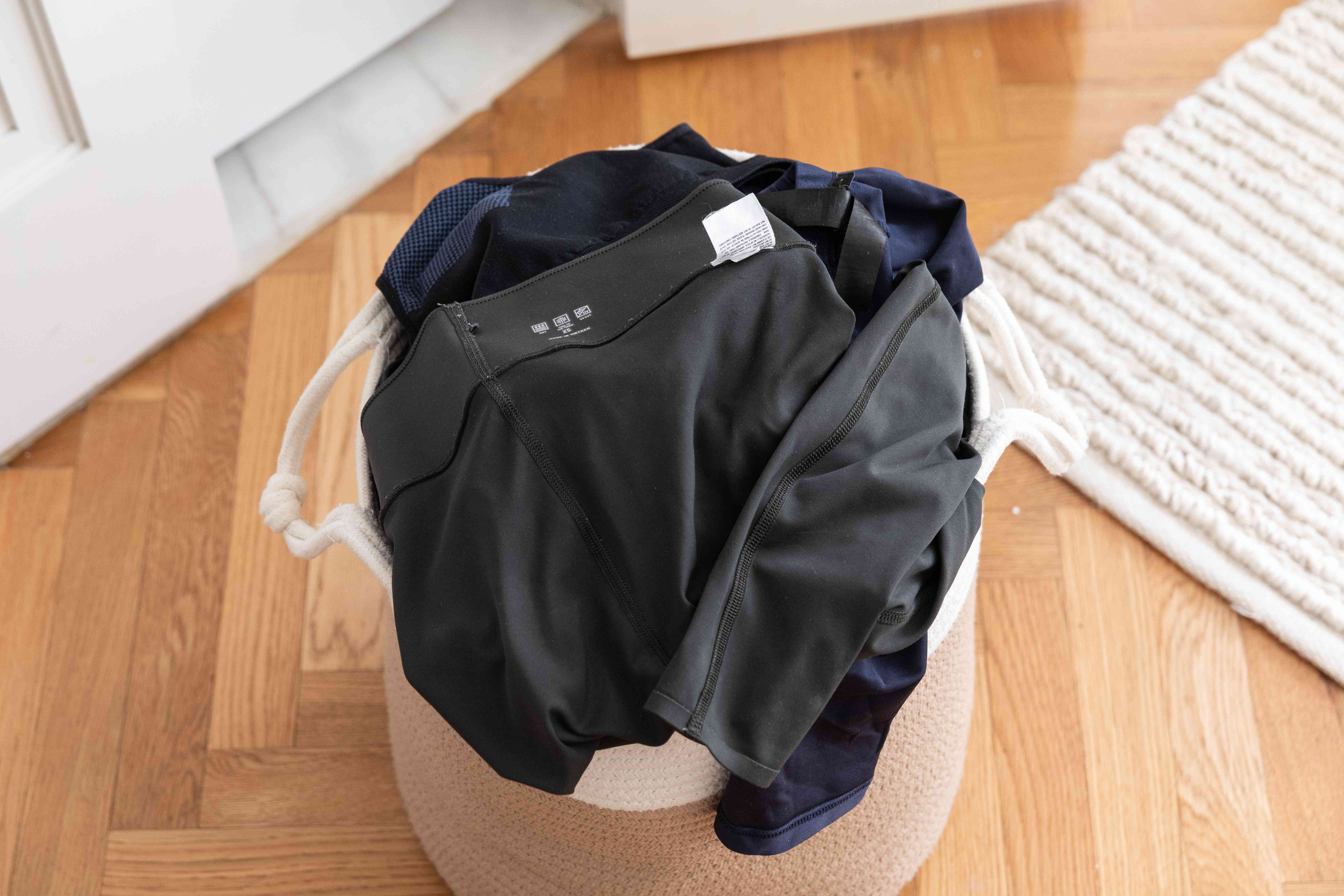 Clothes hamper filled with yoga pants turned inside out for cleaning