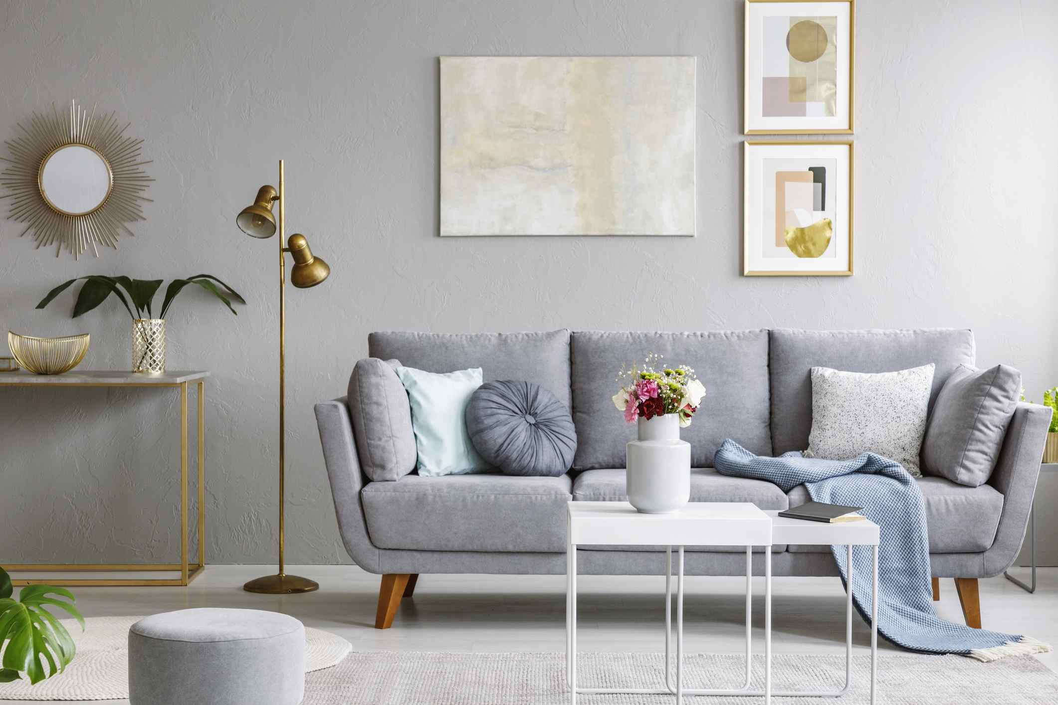 Gold mirror above shelf with plant in grey living room interior with sofa and flowers on table. Real photo