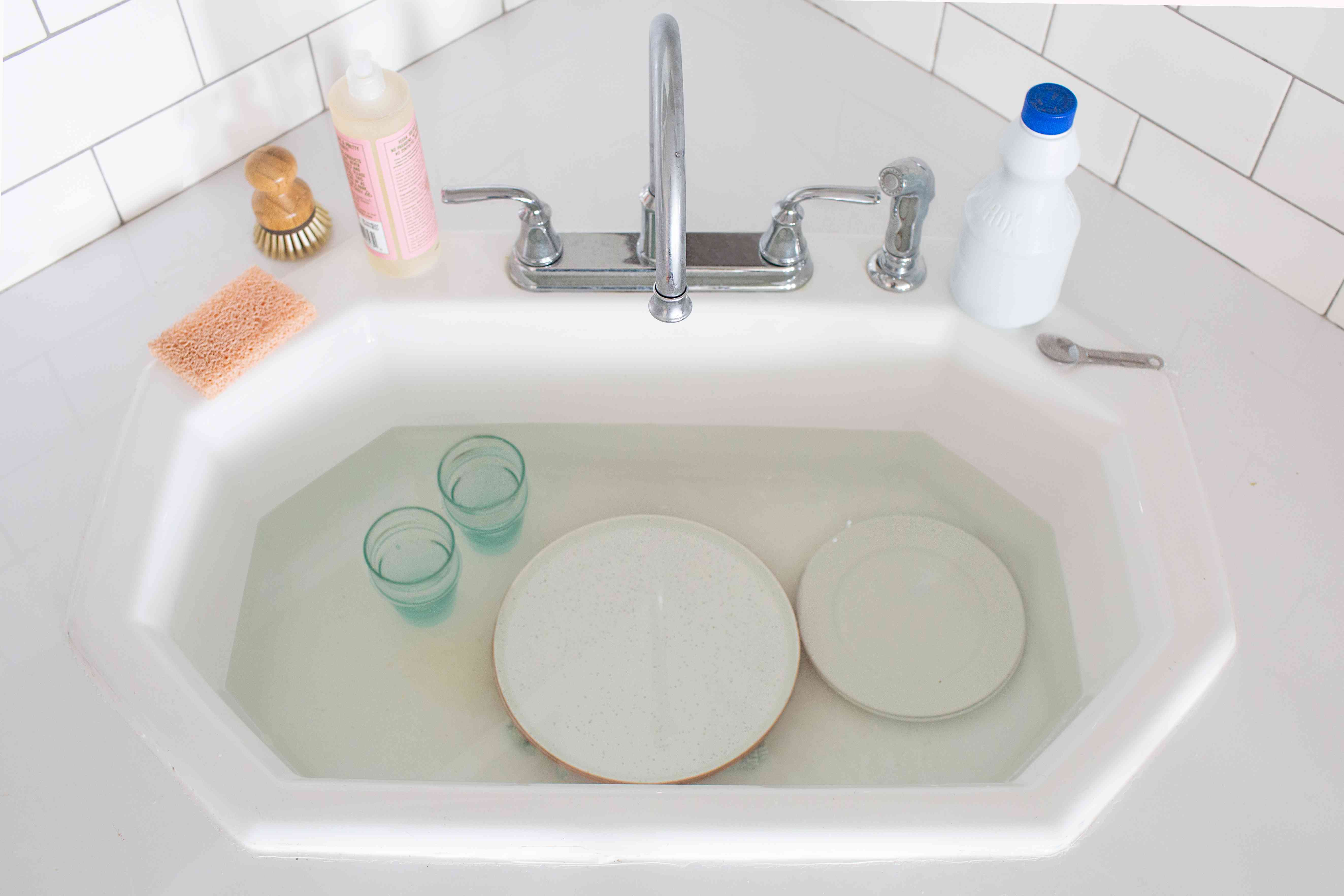 dishes submerged in a bleach solution