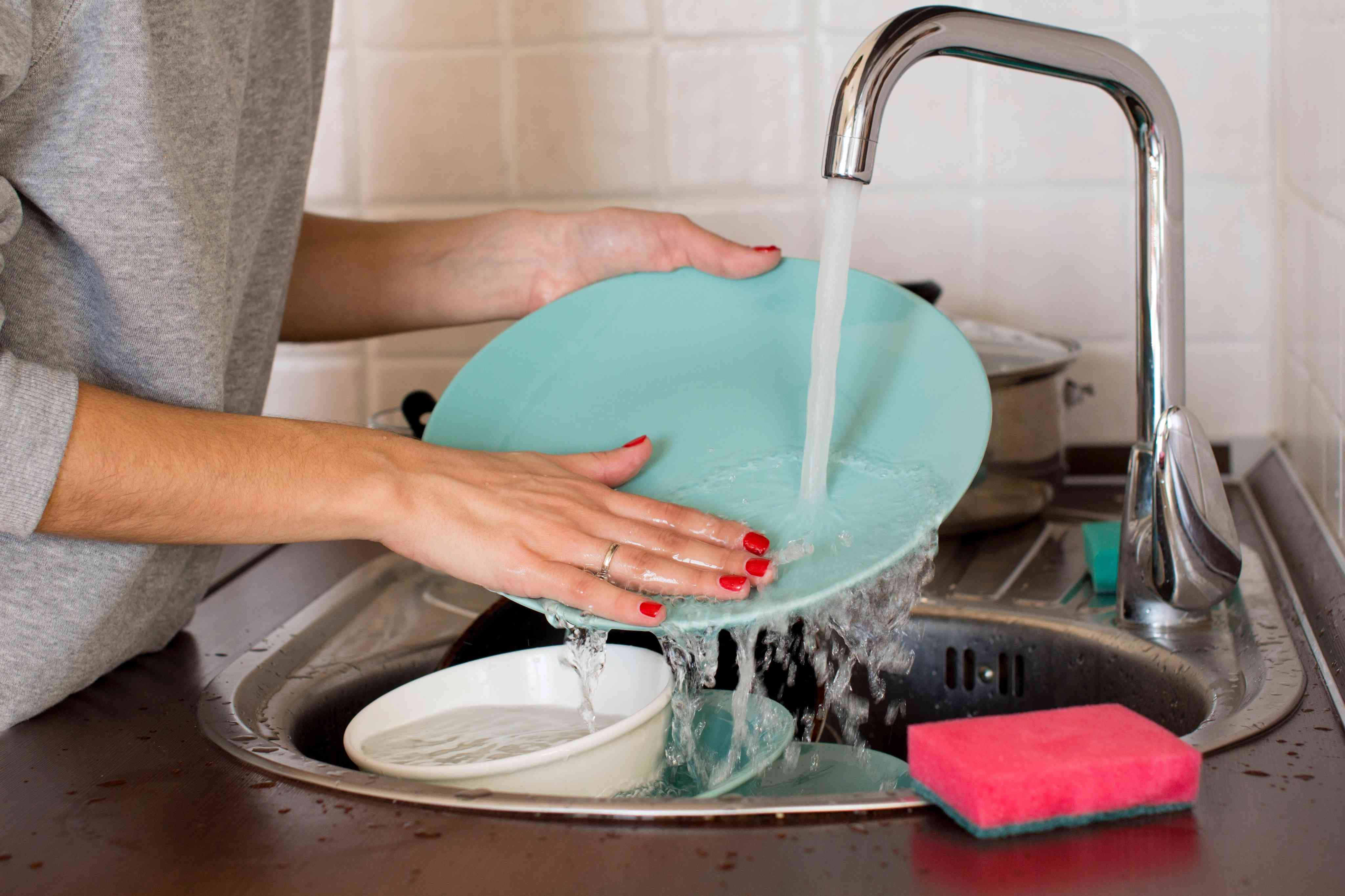 A woman rinsing dishes in the sink