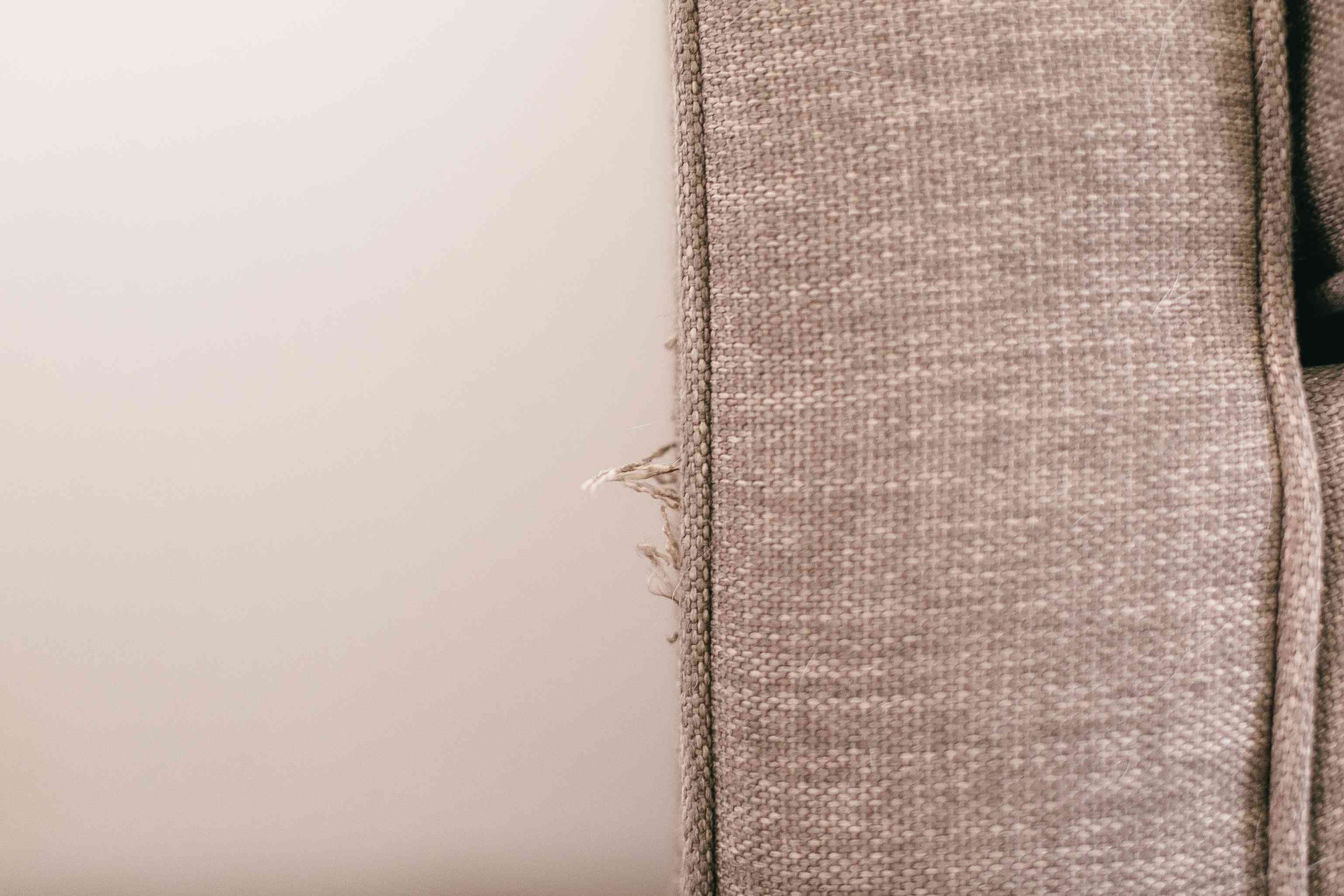 Tan couch upholstery with frayed ends closeup