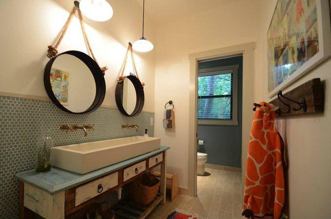 Espejos redondos rústicos sobre un fregadero largo