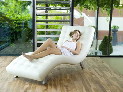 Woman relaxing on reclining chair, looking away