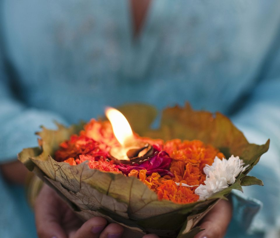 Candle burning among flowers in a leaf bowl