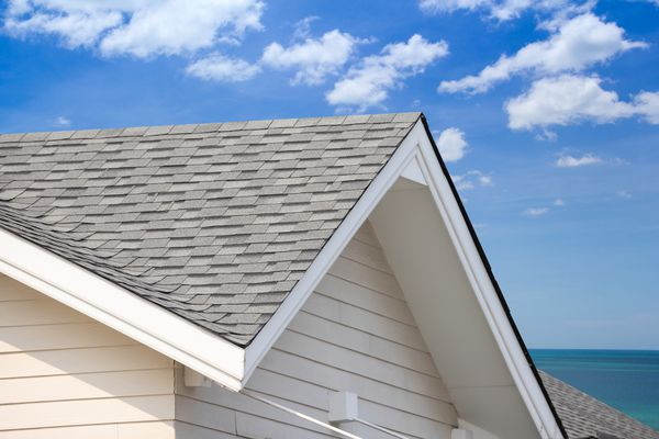 grey roof shingle with blue sky background, house roof near sea in morning time.