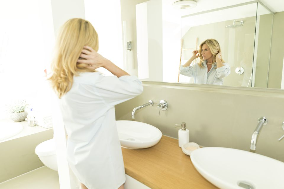 Woman looking at her mirror image in the bathroom