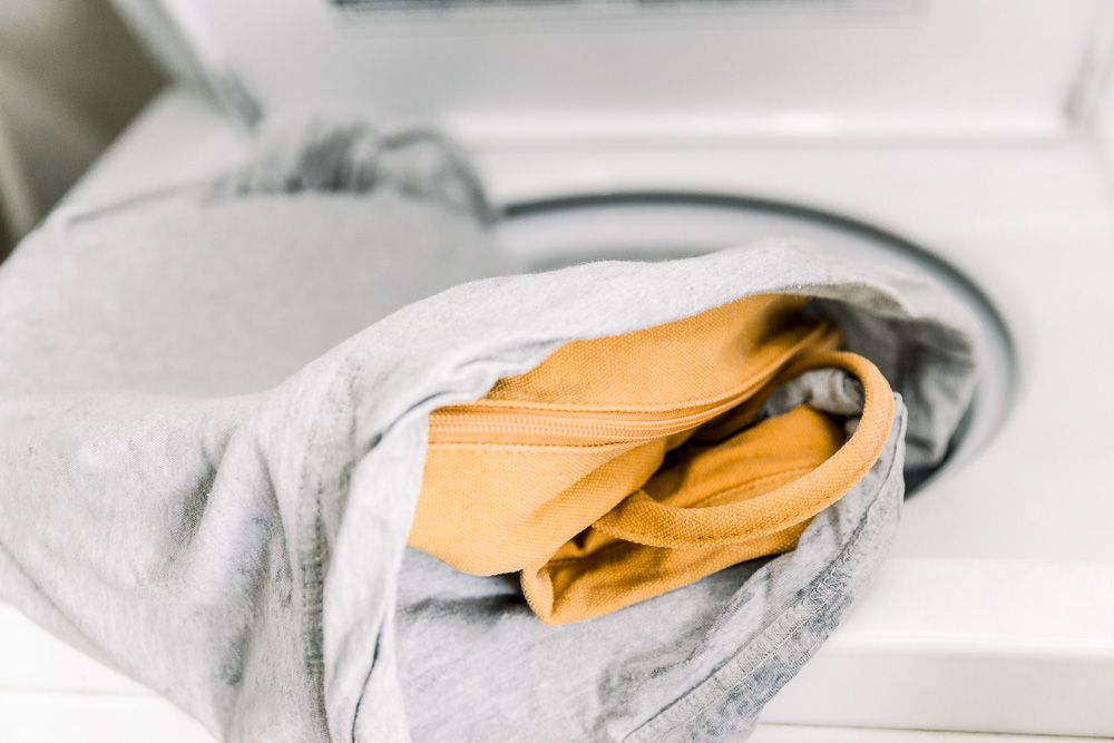 A backpack in a pillowcase on a washer