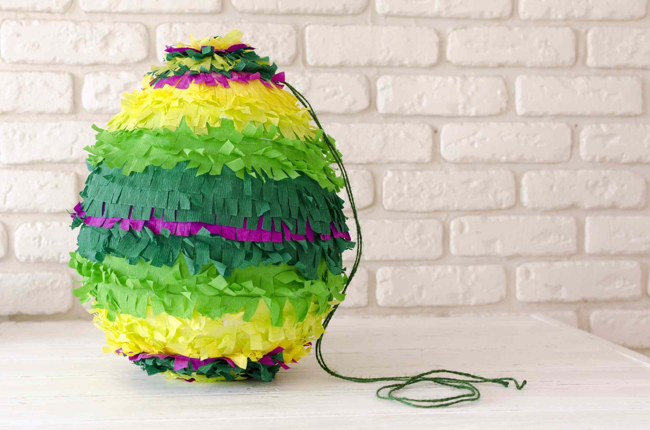 colored paper pinata on white wooden table