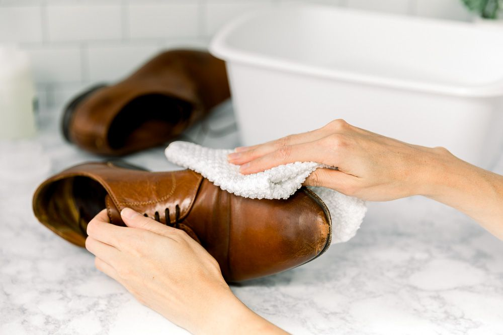 Someone wiping leather shoes with a cloth