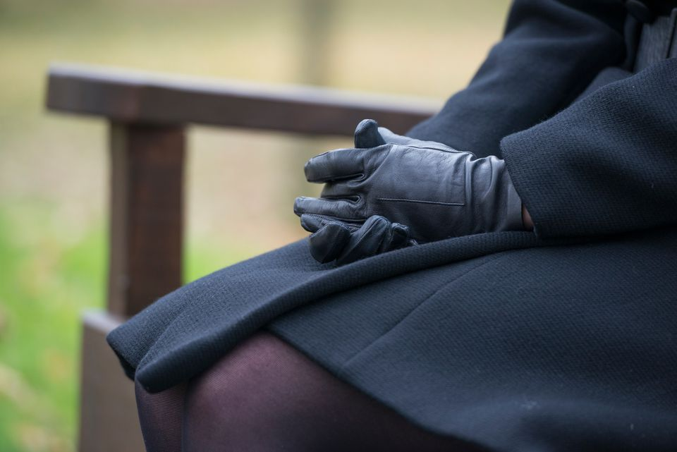Woman in dark coat and dress with black gloves.