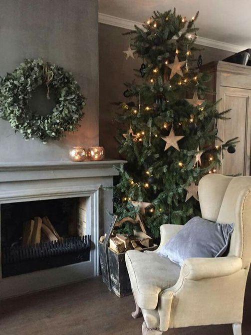 Árbol de Navidad con grandes adornos de estrellas doradas