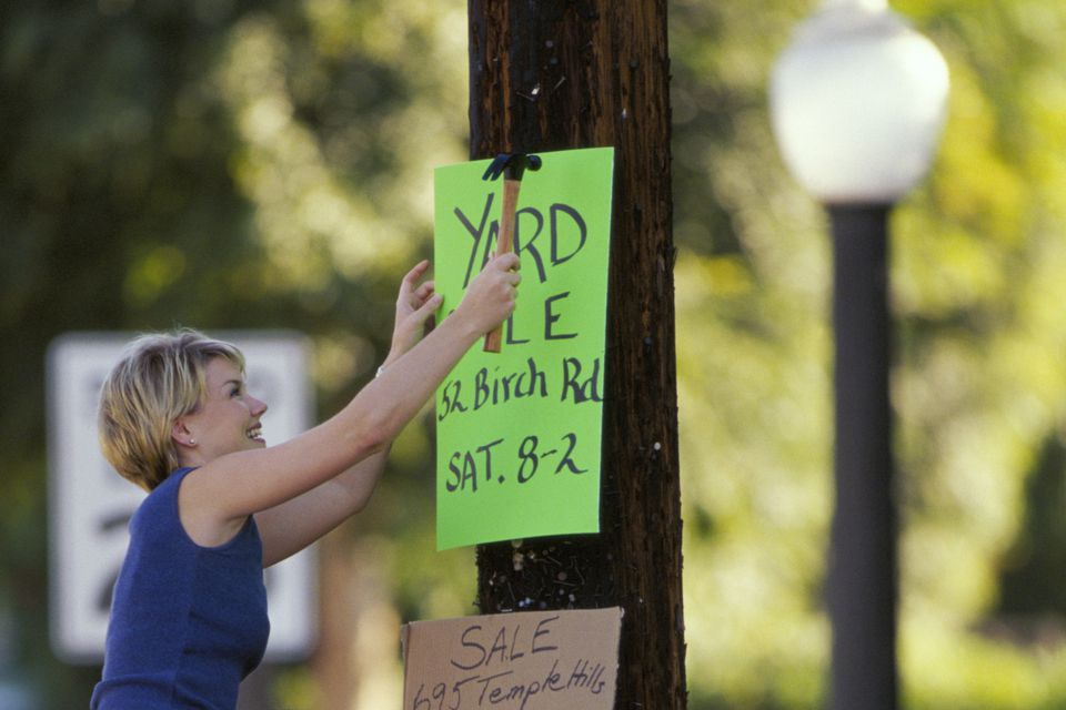 Caucasian woman hanging yard sale sign