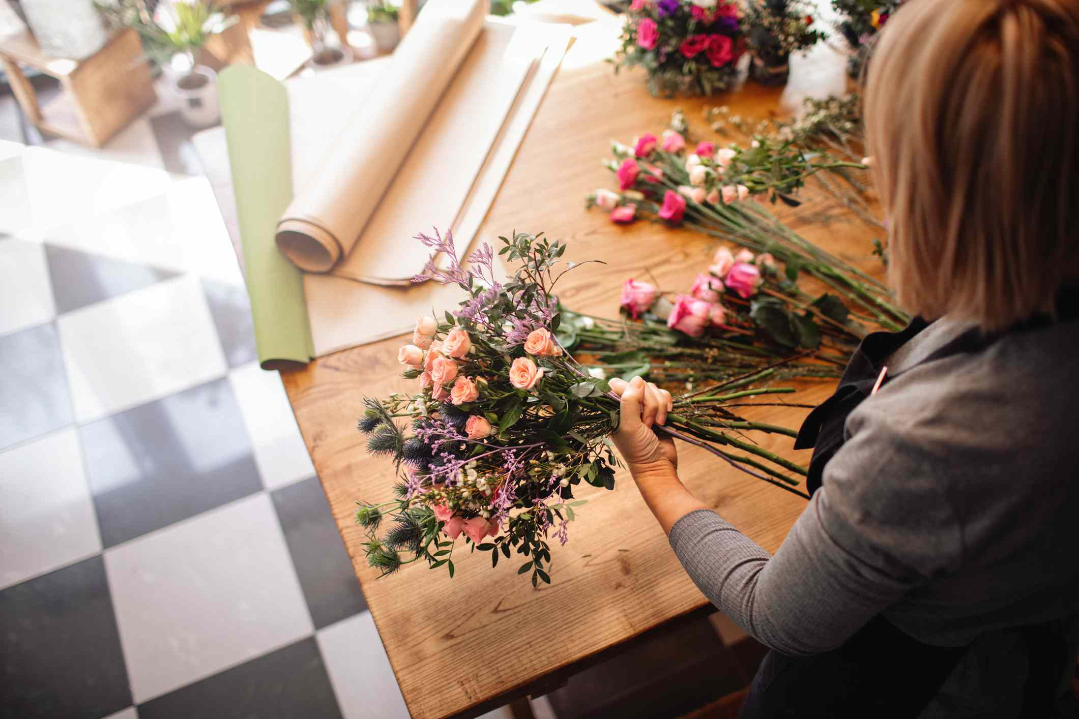 Woman wrapping flower bouquets in brown paper.