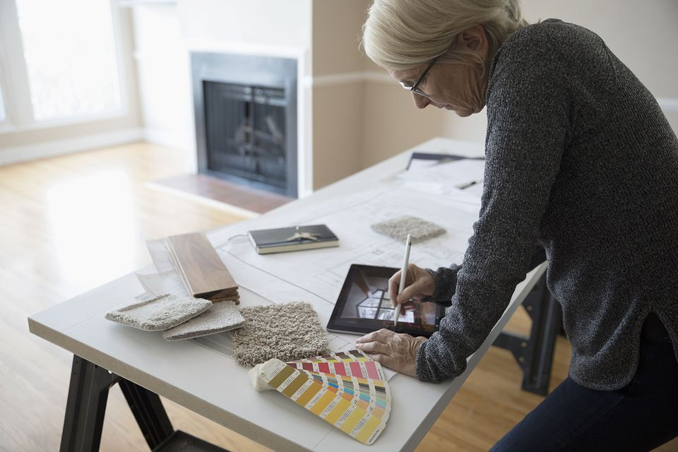 Senior Female Interior Designer Planning Remodel Using Digital Tablet Augmented Reality