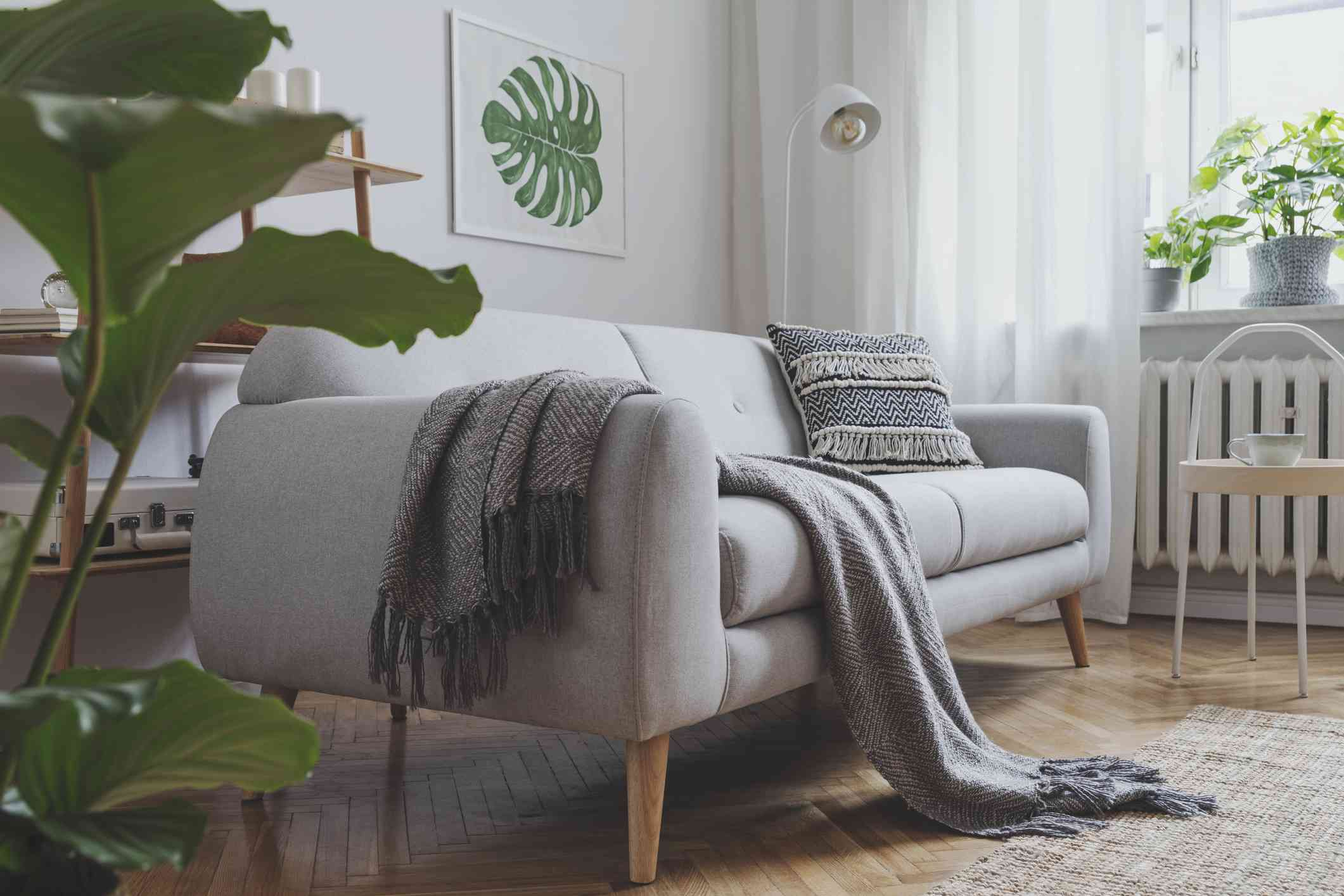 Stylish scandinavian living room with design sofa, poster, plants, bookstand, coffee table, cozy blanket and mock up frames. White background walls, brown wooden parquet and modern lamp