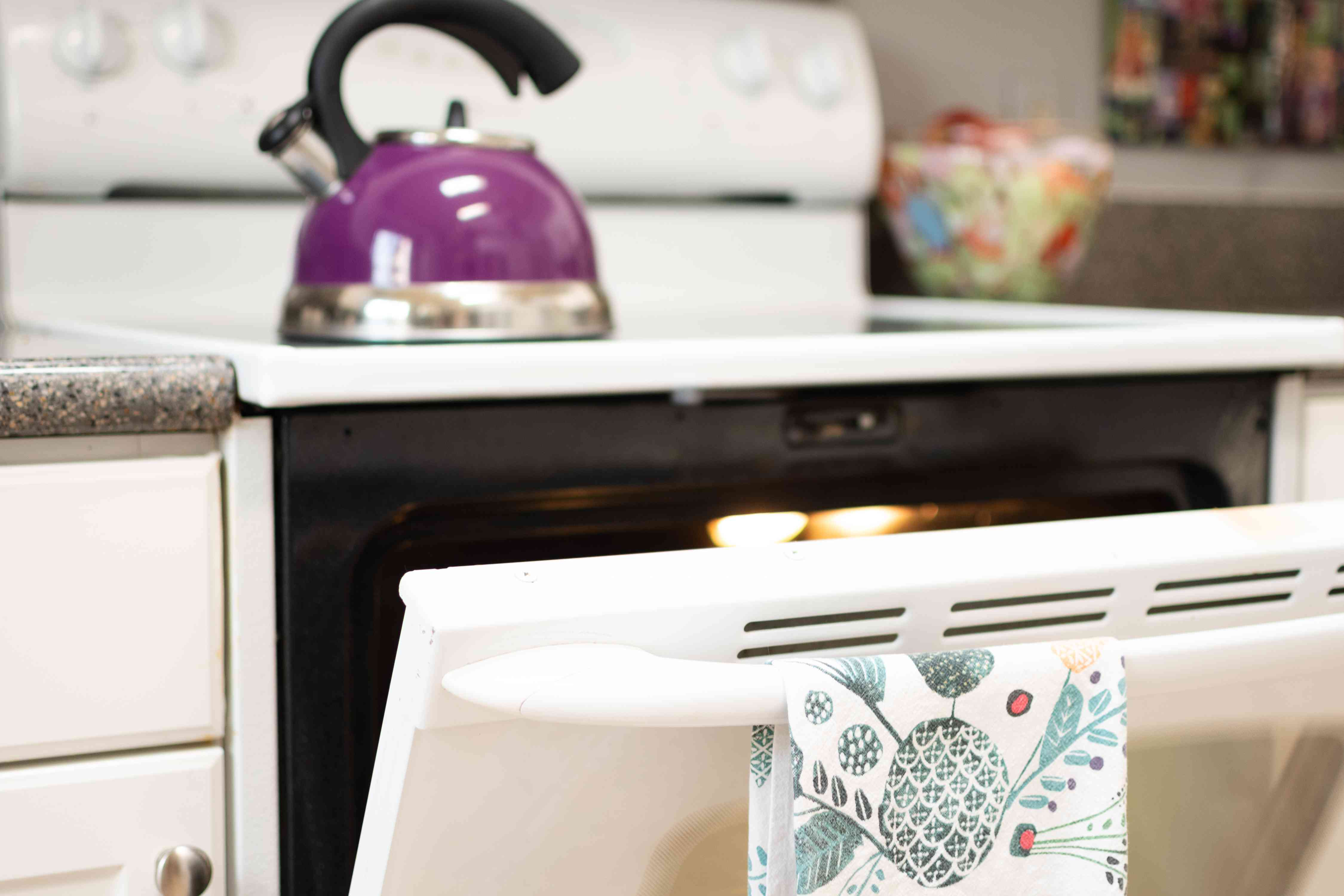 Oven door open with patterned towel hanging and purple teapot on top of stove