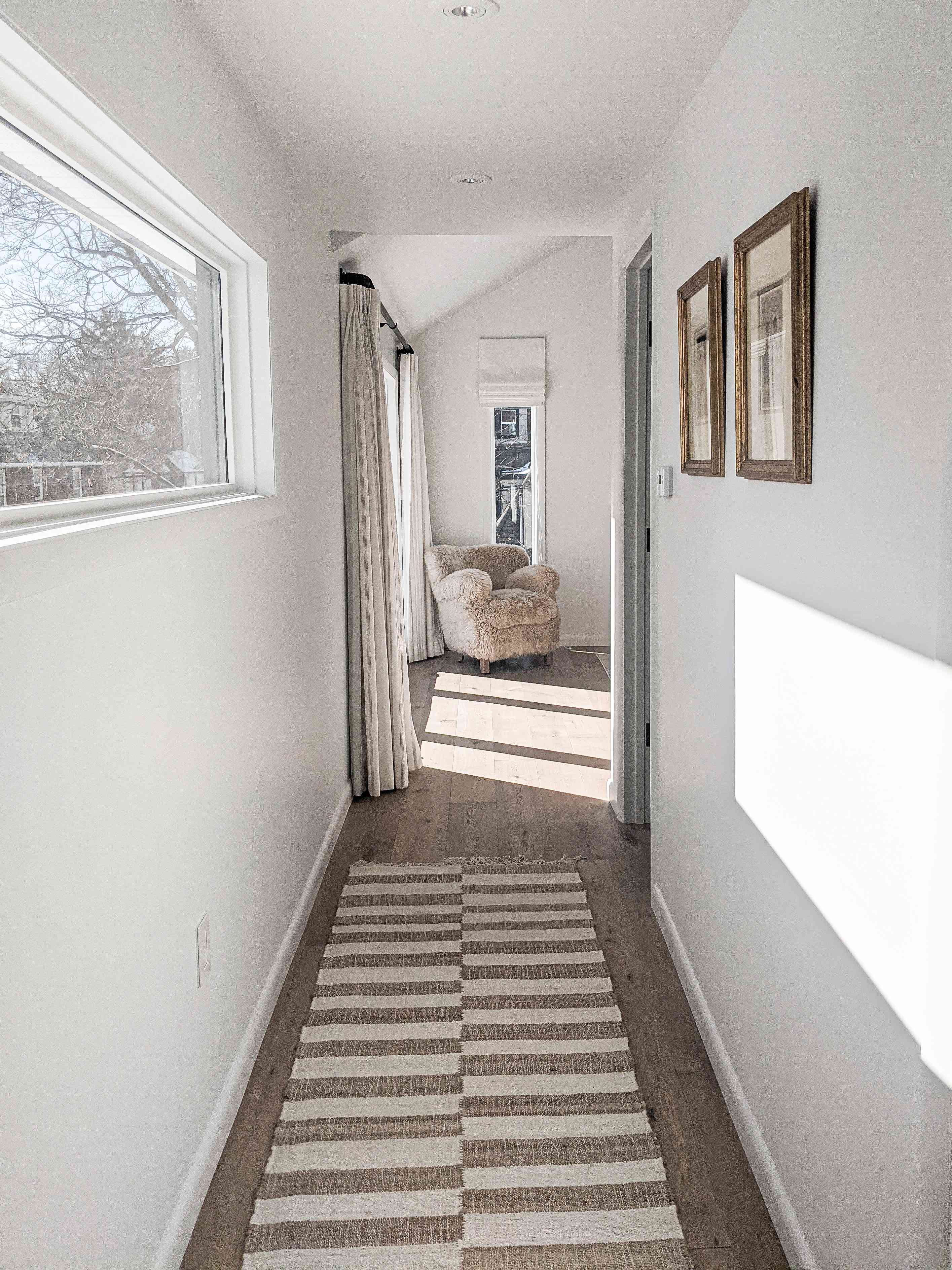 A hallway in the home of Molly & Fritz features a bright window