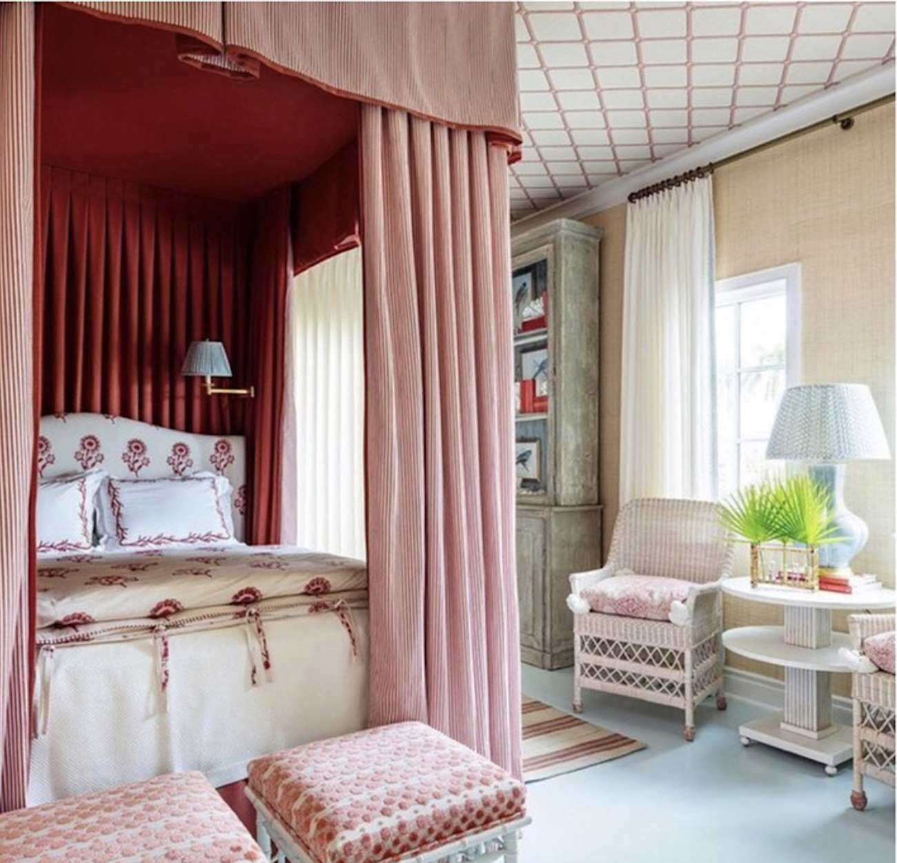 bedroom with red and pink colors against cream walls and wicker furniture