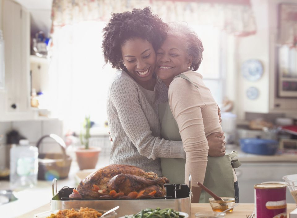 Mother and daughter embracing over cooked turkey