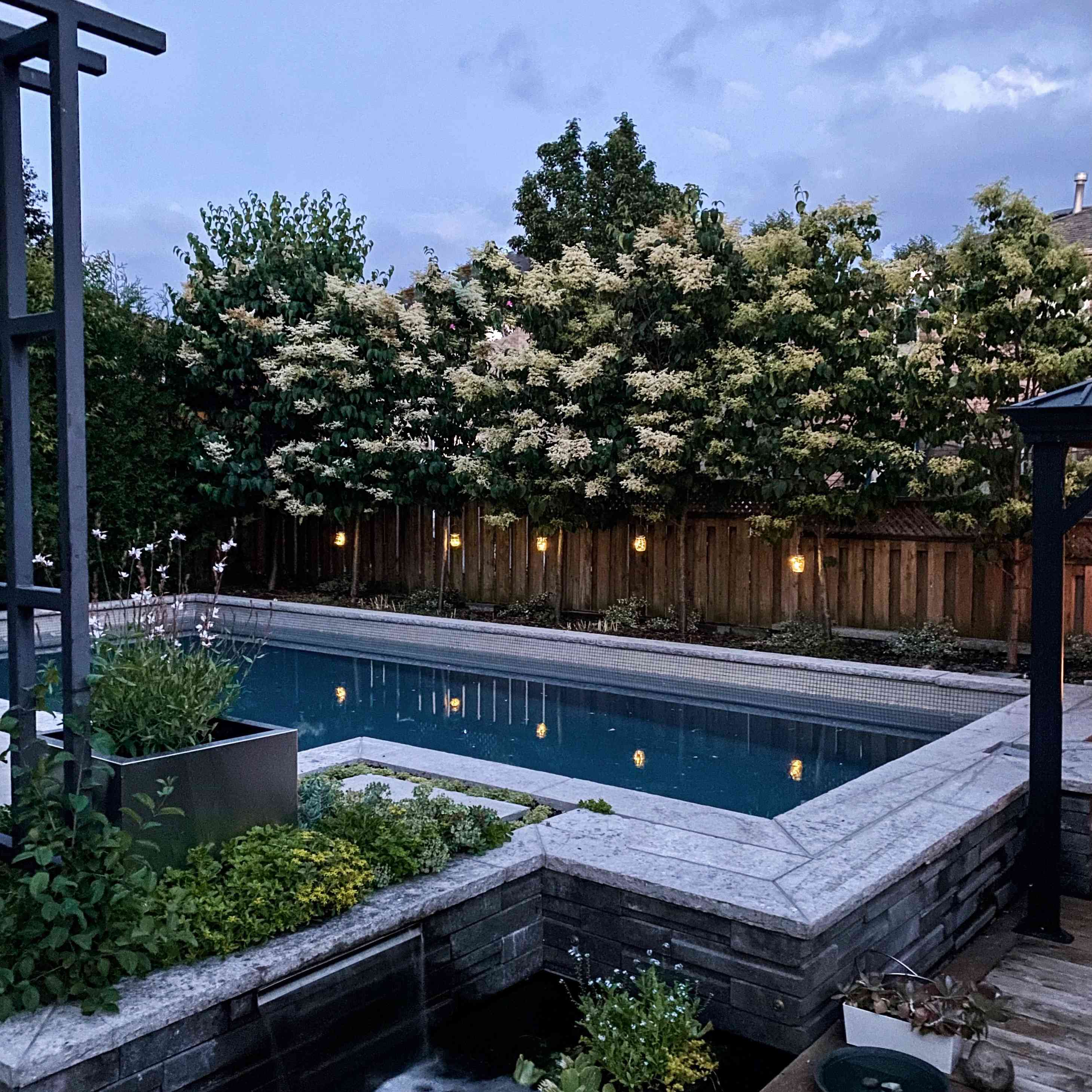 a pool is surrounded by lush greenery and a blooming tree behind the fence