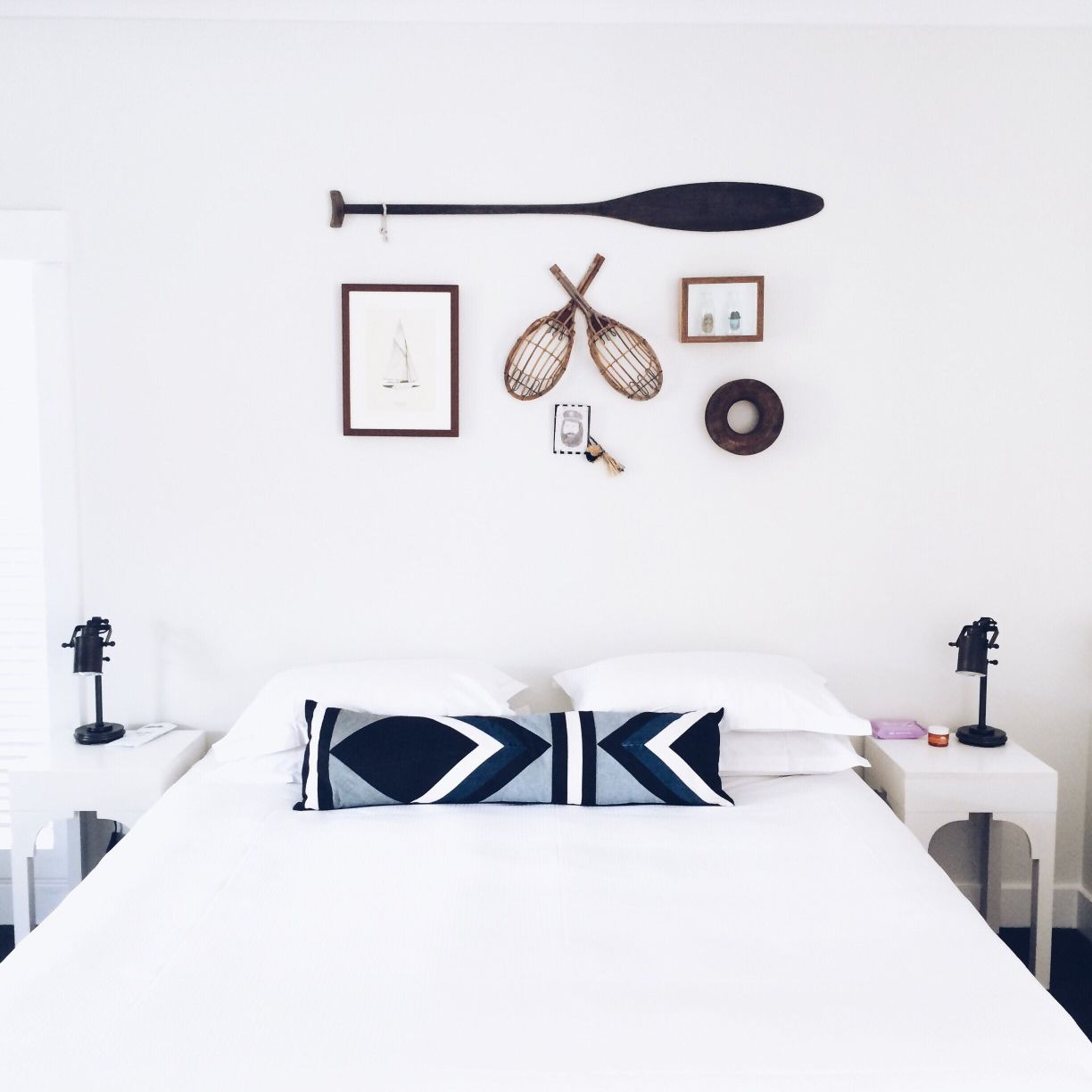 bed with white linens and an oar hanging over it