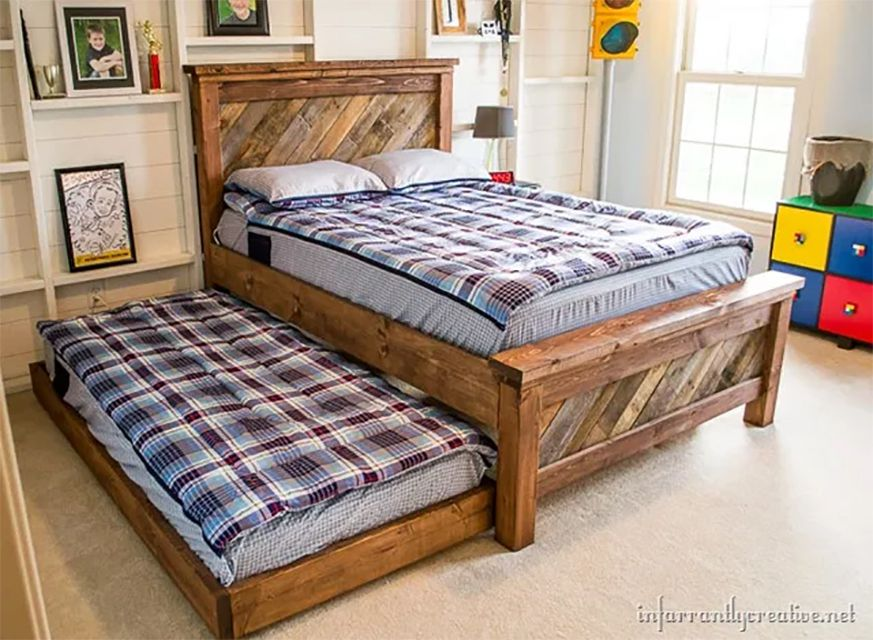 A bed and trundle made out of pallets in a bedroom