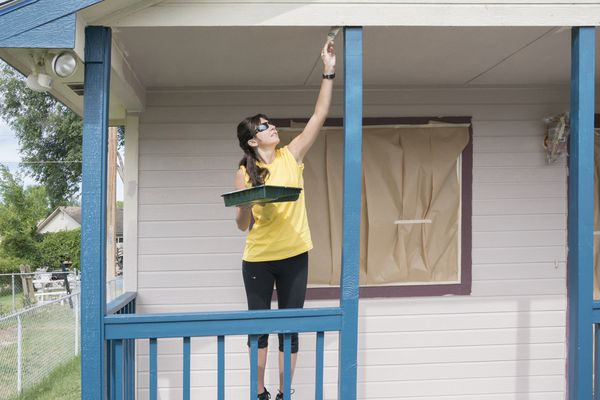 Woman painting porch of house