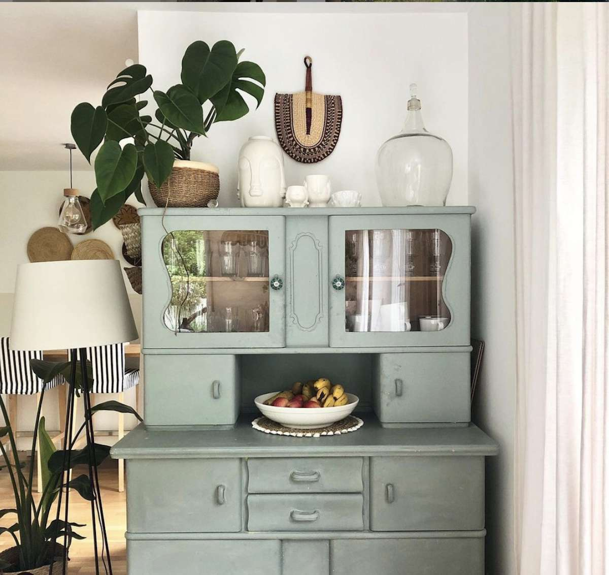 vintage teal dresser with plant and small knick knacks sitting in top placed in corner