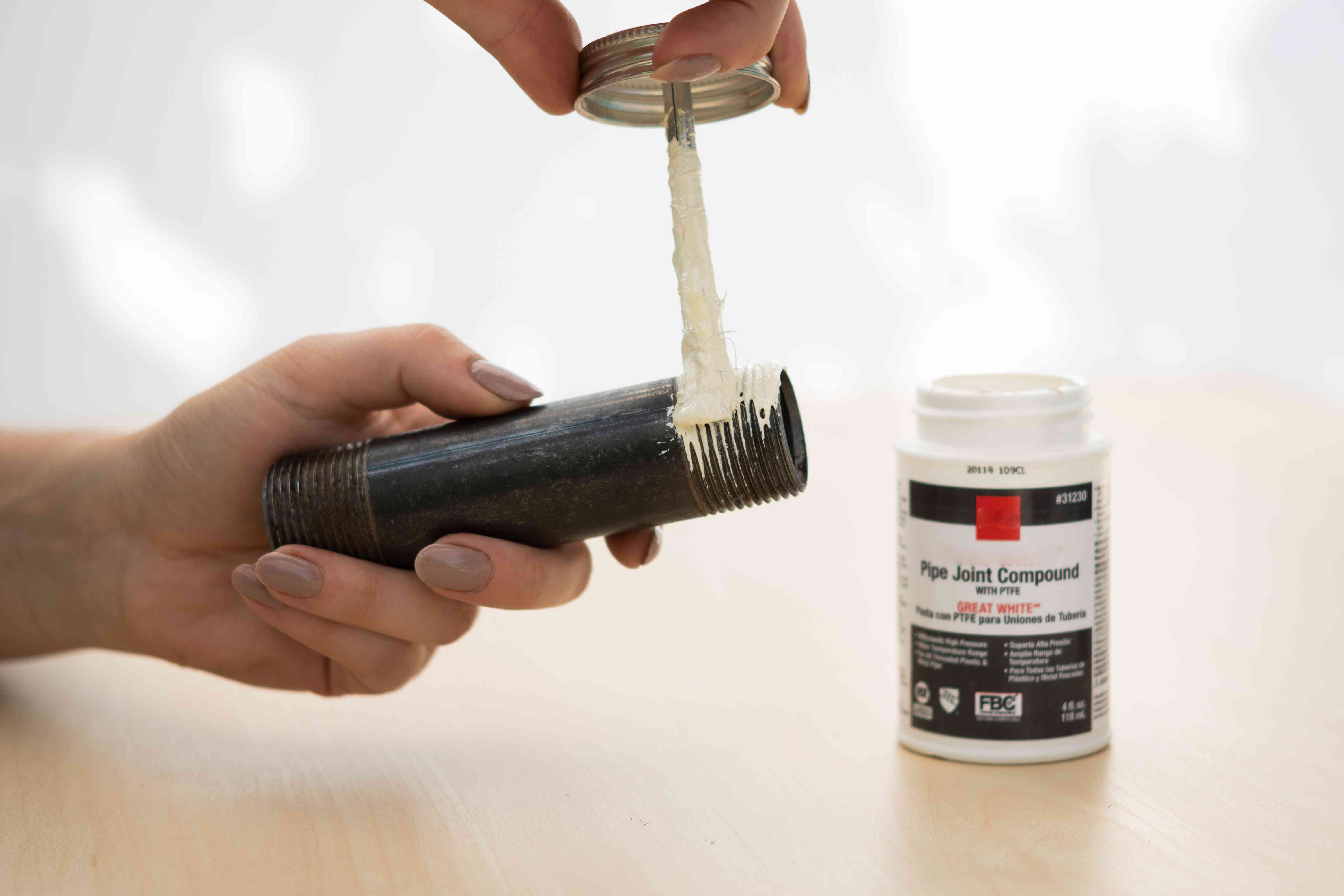 White pipe dope spread across pipe threads with applicator brush